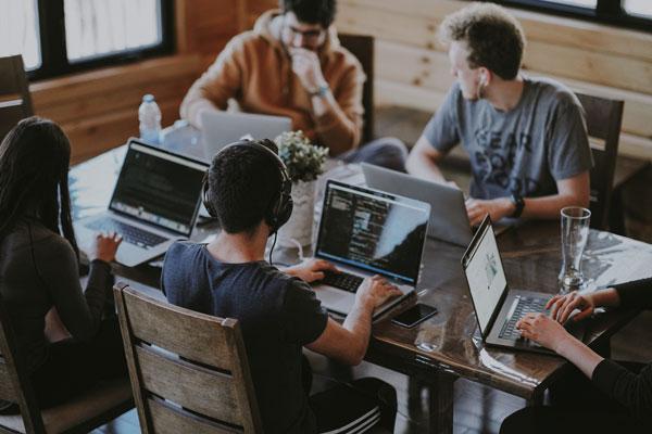 Inovacije novoosnovanih MSP-ova - 5ljudi sjedi za stolom i rade na laptopu