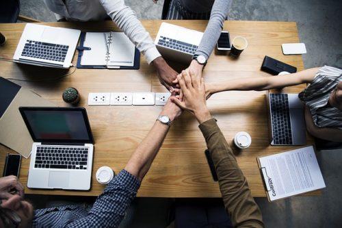 Eu fondovi Partnerstvo 5 ljudi u uredu za stolom i držr euke jednu preko druge