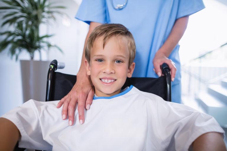 SOCIJALNI FOND- dijete u kolicima a žena iza njega i drži mu ruku na ramenu