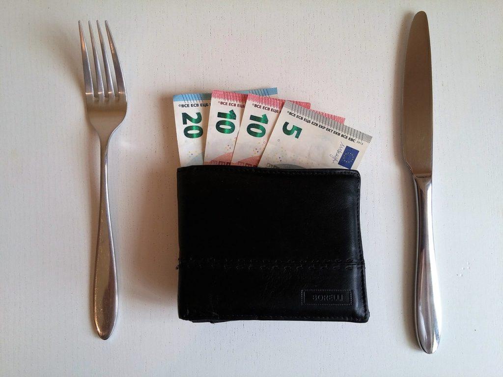 Priprema EU projekata i natječaja - servirani novčanik s novačanicama od 5, 10 i 20 eura i nož i vilica sa strane kao jelo.