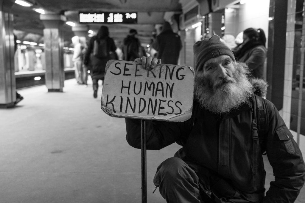 Socijalni fond - Čovjek na kolodvoru s velikom bradom prosi i drži natpis seeking human kindness
